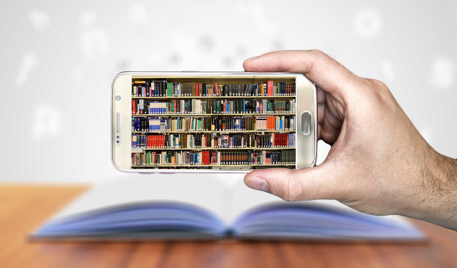Smart phone with picture of library books held by a human hand with a hardcover book in the background