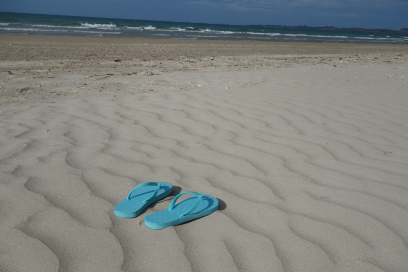 Pair of blue thongs on empty beach, white sand, waves and blue sky in the background