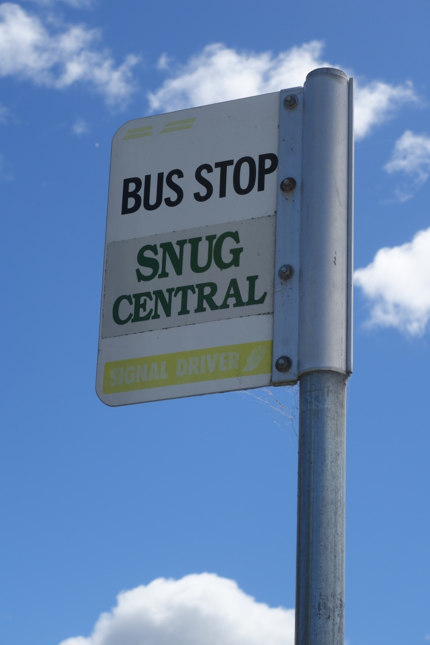 Bus stop road sign for Snug Central in Tasmania with blue sky in the background