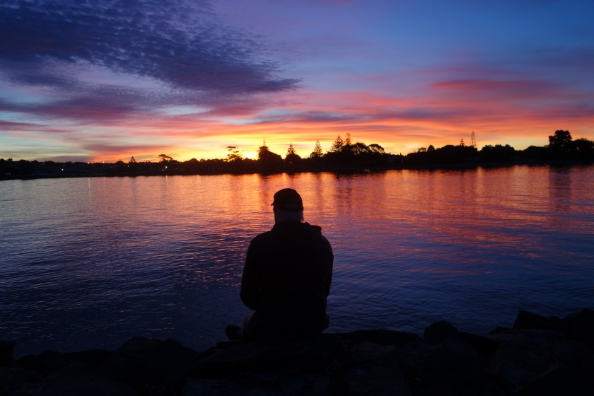 A silhoutted man sits on the bank as sunset lights up the sky in pink and gold on the Mersey River in Devonport Tasmania.