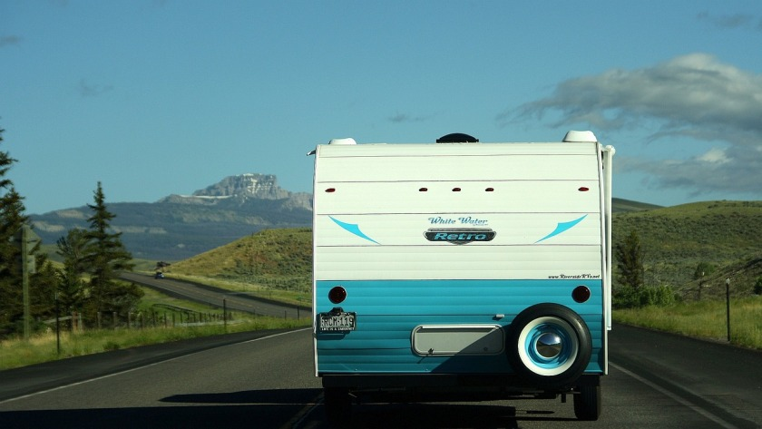 Blue and white caravan on the road with trees and mountains in the distance, blue sky and clouds