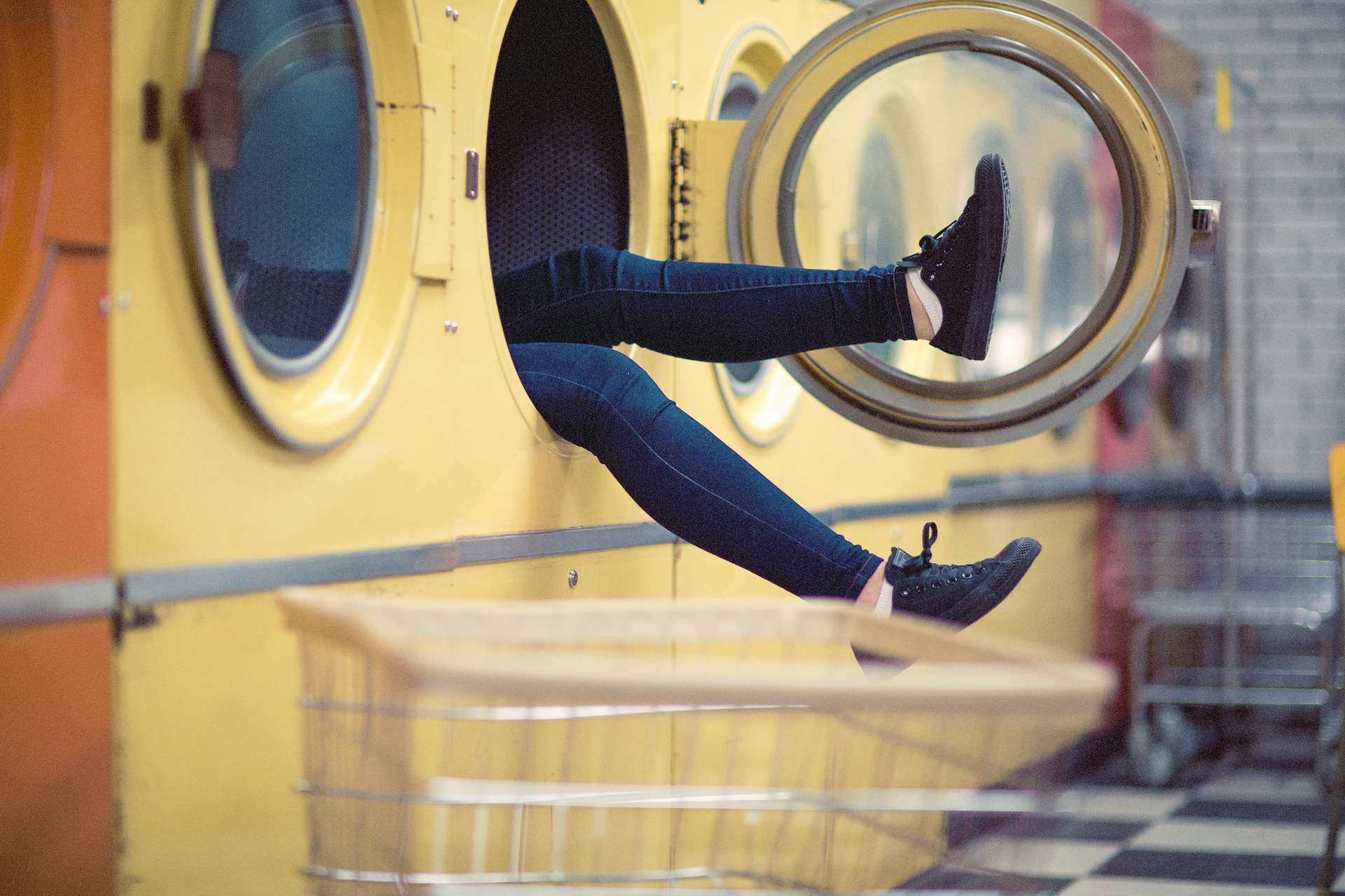 A pair of legs in jeans sticking out from and industrial dryer in a laundromat