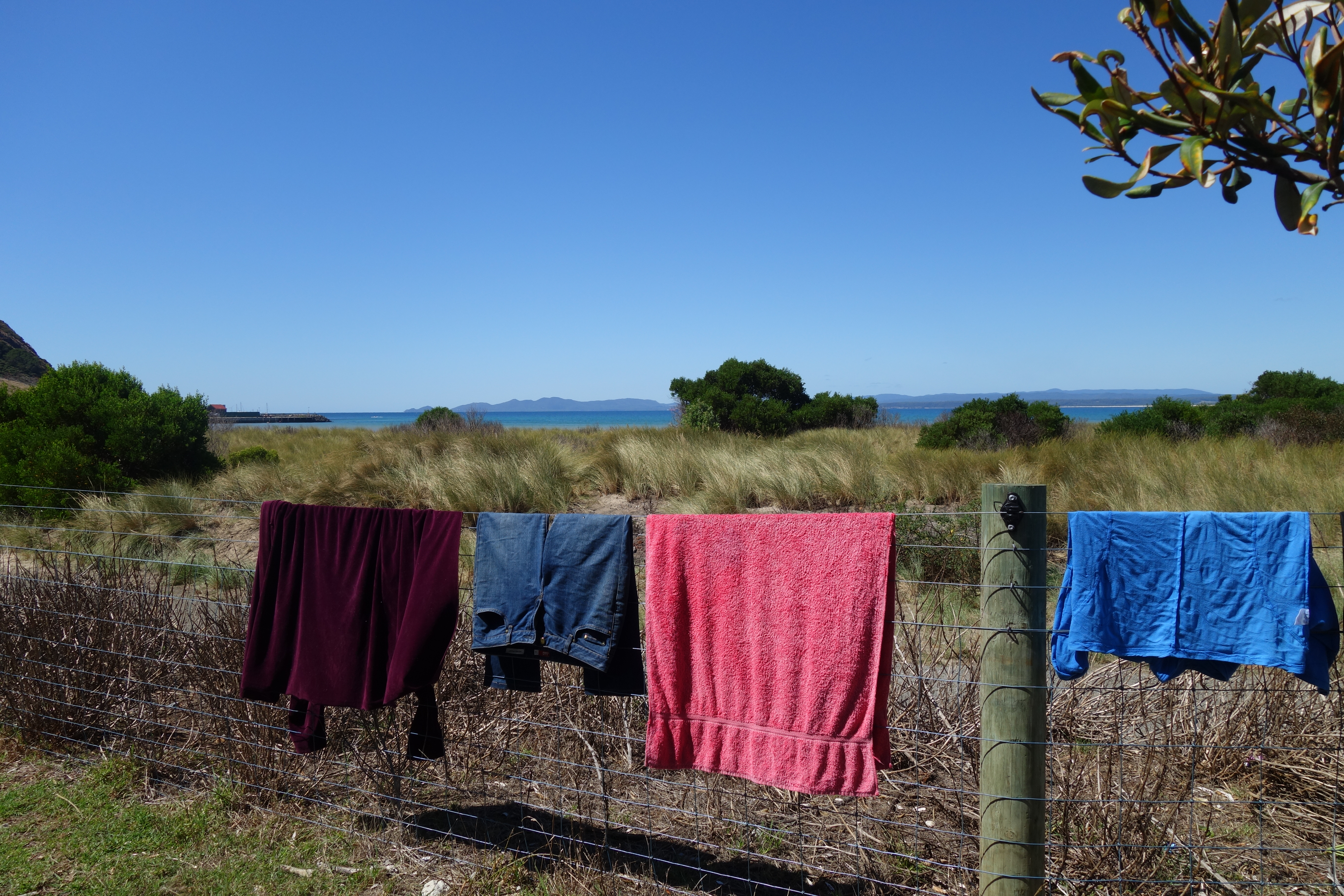 Washing hanging on a wire fence with sea and mountains in the background